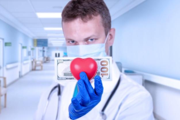 Lekarz posiada czerwone serce i banknot stu dolarowy.