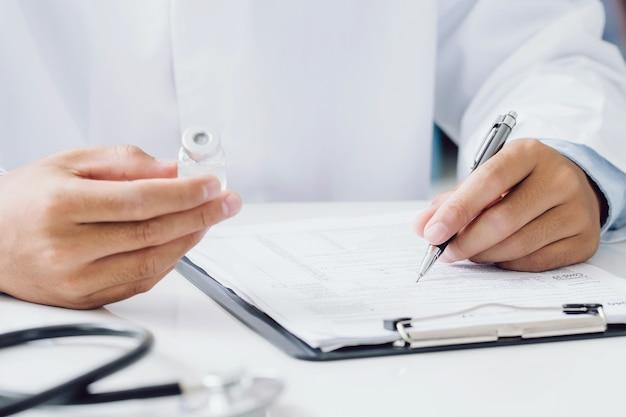 Lekarz posiadający butelkę recepty i pisanie recepty na specjalnym formularzu w sali biurowej. koncepcja opieki zdrowotnej, szczepionki, medycyny i farmacji.