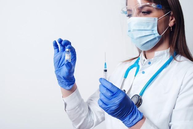 Lekarz posiadający butelkę szczepionki coronavirus i strzykawki medycyny wtrysku szczepionka koncepcja walki z koronawirusem. szczepienie w celu ochrony koronawirusa. czas na szczepienie 2021. skopiuj miejsce.