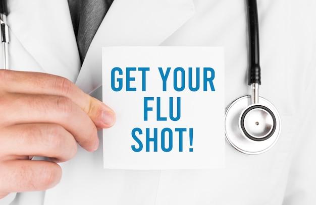 Lekarz posiadający kartę z tekstem zdobądź szczepionkę na grypę, pojęcie medyczne