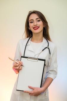 Lekarz posiadający schowka z piórem. ładna kobieta w formie medycznej uśmiechnięta