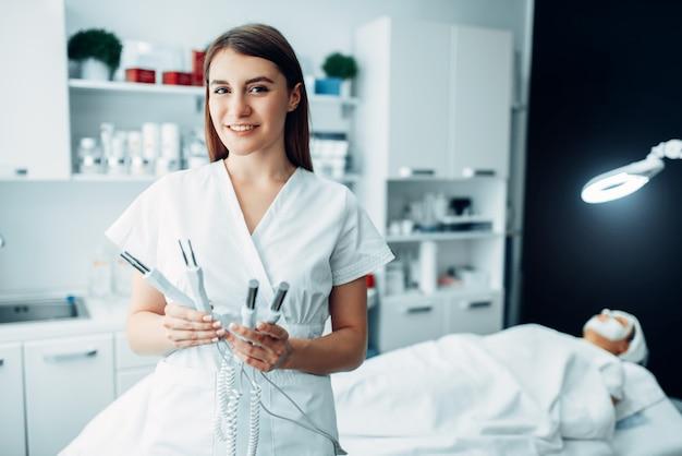 Lekarz pozuje ze sprzętem, gabinet kosmetologii