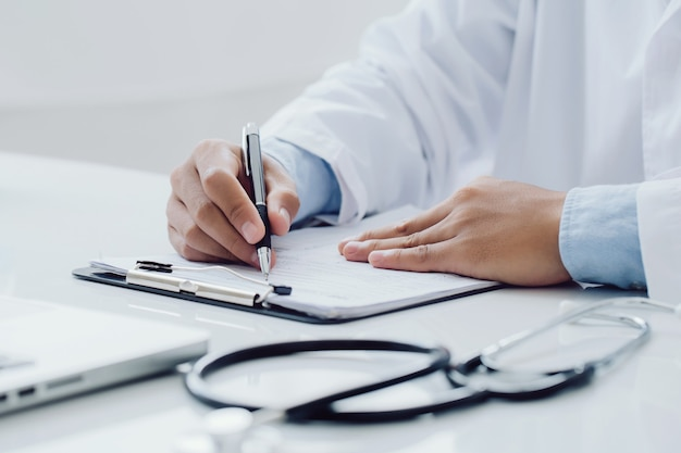 Lekarz pracujący w szpitalu piszący receptę na biurku, koncepcja opieki zdrowotnej i medycznej, wyniki badań w tle