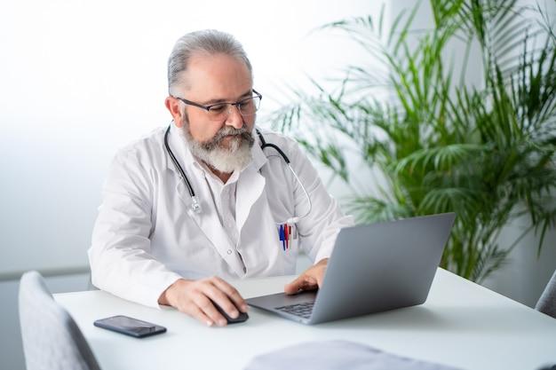 Lekarz pracujący z laptopem i prowadzący wideokonferencję z pacjentem