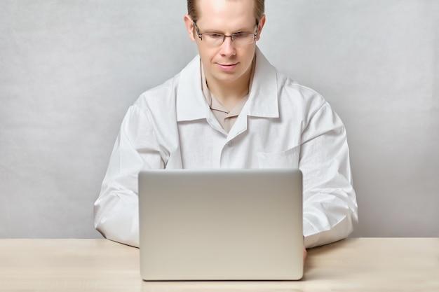 Lekarz pracuje na laptopie i odpowiada na pytania klientów online.