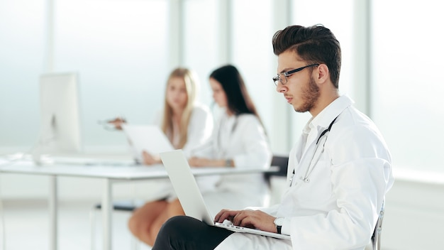 Lekarz pracuje na laptopie w szpitalnym pokoju. zdjęcie z miejsca na kopię