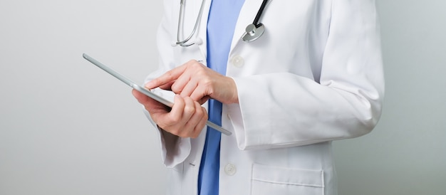 Lekarz pracuje z nowoczesnym cyfrowym tabletem i komputerem dla sieci telekomunikacji medycznej, aby skonsultować i przepisać lek.
