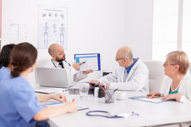 Lekarz praktykujący przedstawiający prezentację ekspertyzy medycznej w schowku omawiający diagnozę choroby z pracą zespołową w leczeniu