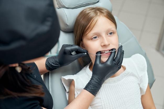 Lekarz próbuje aparaty ortodontyczne dla dziewczynki.