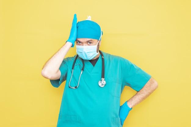 Lekarz przebrany za chirurga na zielono ze stetoskopem i maską na żółtym tle z zmartwioną miną.