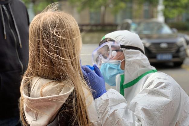 Lekarz przeprowadzający test koronawirusa u dziewczynki z wacikiem medycznym