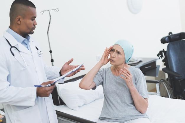 Lekarz przesłuchuje kobietę poddawaną rehabilitacji.