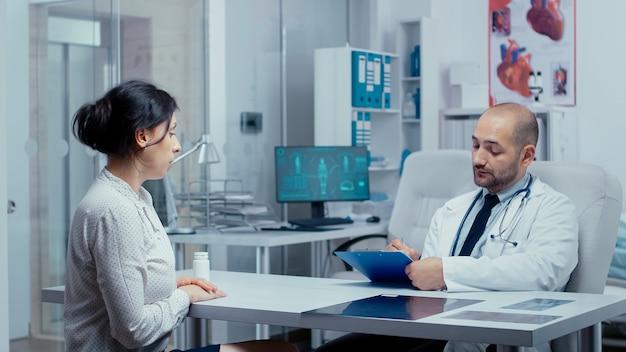 Lekarz przesłuchuje młoda pacjentka w swoim biurze, pisząc answears w schowku. opieka zdrowotna w nowoczesnym szpitalu lub przychodni prywatnej, profilaktyka chorób i konsultacje w gabinecie lekarskim leczenie med