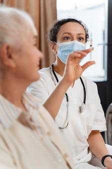 Lekarz przygotowuje szczepionkę dla starszej kobiety