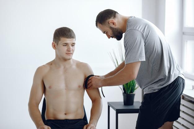 Lekarz przykleja tipi do sportowca w szpitalu