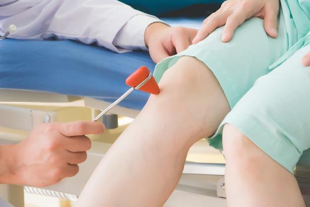 Lekarz puka młotkiem starszego pacjenta, aby sprawdzić reakcję kontrolowaną przez autonomiczny układ nerwowy.