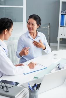 Lekarz pyta starszej wietnamskiej kobiety o jej dolegliwości podczas wypełniania formularza w schowku