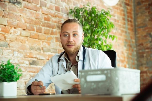 Lekarz rasy białej konsultacji dla pacjenta, pracuje w gabinecie