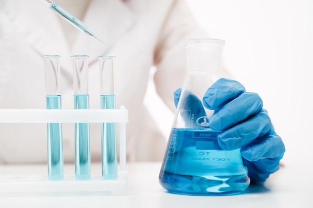 Lekarz ręce w niebieskich rękawiczkach trzymających kolbę erlenmeyera z niebieskim płynem wykonującym test na koronawirusa w laboratorium