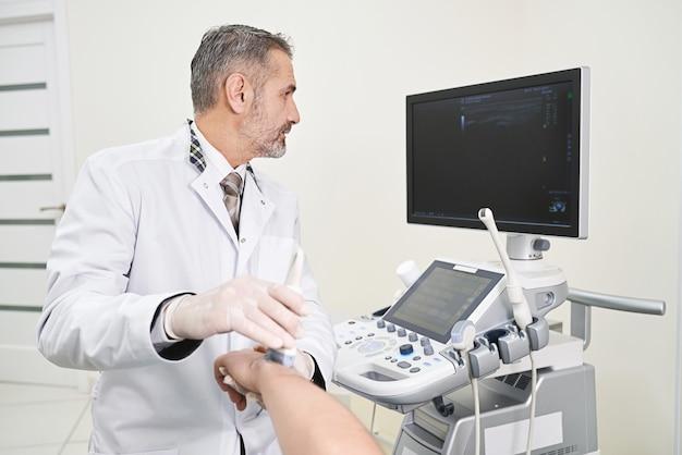 Lekarz robi badanie ultrasonograficzne nadgarstka patinet.