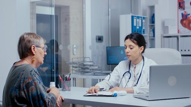 Lekarz robi kontrolę temperatury w gabinecie do starszej pacjentki na emeryturze. opieka zdrowotna w nowoczesnym szpitalu lub przychodni prywatnej, profilaktyka chorób i konsultacje w gabinecie lekarskim leczenie leki di
