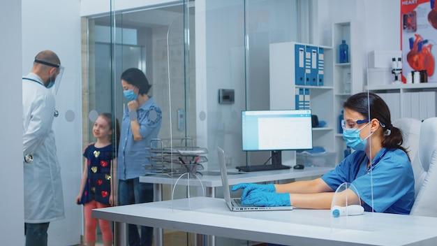 Lekarz robi notatki w schowku na dane osobowe pacjentów podczas covid-19. lekarz specjalista medycyny w masce ochronnej udzielający świadczeń zdrowotnych, konsultacji, leczenia w przychodni szpitalnej