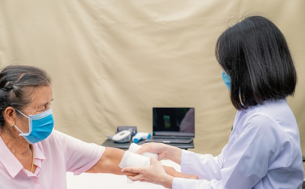 Lekarz robi ranę na ramieniu starszej kobiety, która uległa wypadkowi.