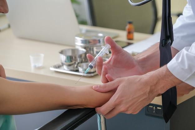 Lekarz robi zastrzyk pacjentowi