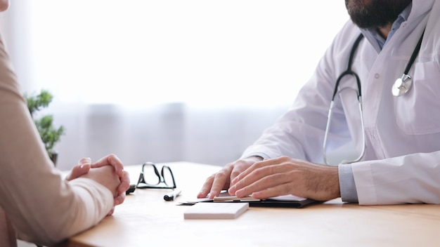 Lekarz rodzinny i pacjent rozmawia w gabinecie lekarskim.