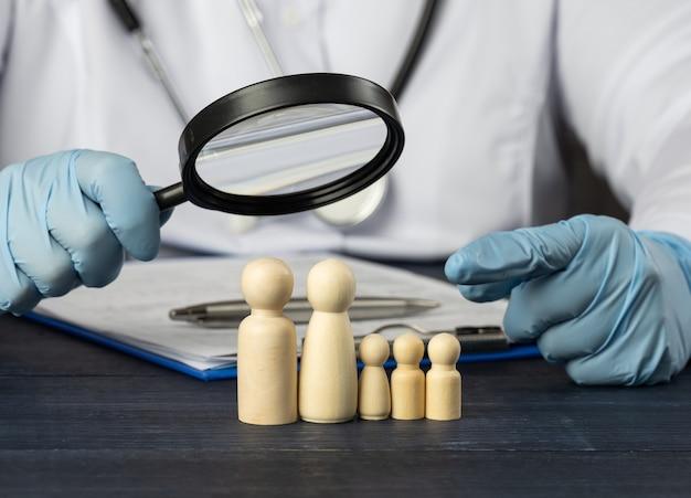Lekarz rodzinny trzyma lupę nad drewnianą figurką. koncepcja badań medycznych, metody leczenia. potrzeba ubezpieczenia medycznego