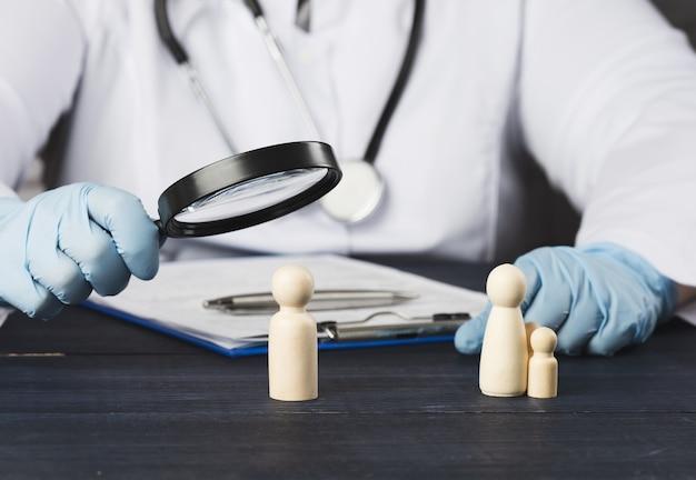 Lekarz rodzinny trzyma lupę nad drewnianą figurką