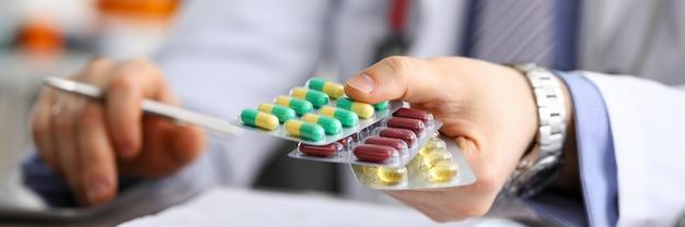 Lekarz rodzinny w klinice trzymając paczkę różnych pęcherzyków z bliska. praktyka przepisywania leków ratujących życie i legalna koncepcja apteki
