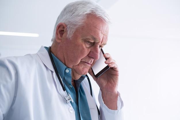 Lekarz rozmawia przez telefon komórkowy w korytarzu