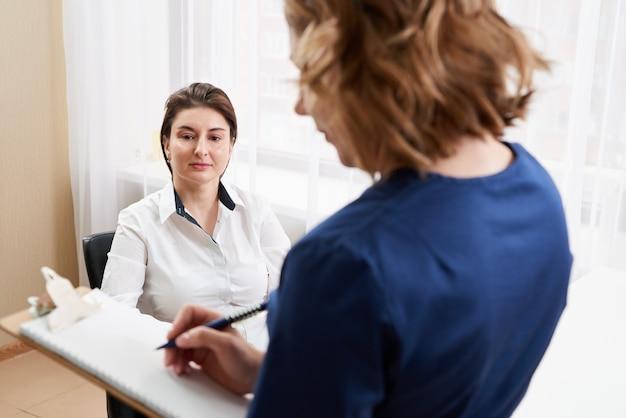 Lekarz rozmawia z młodą pacjentką i robienie notatek stojąc w swoim biurze