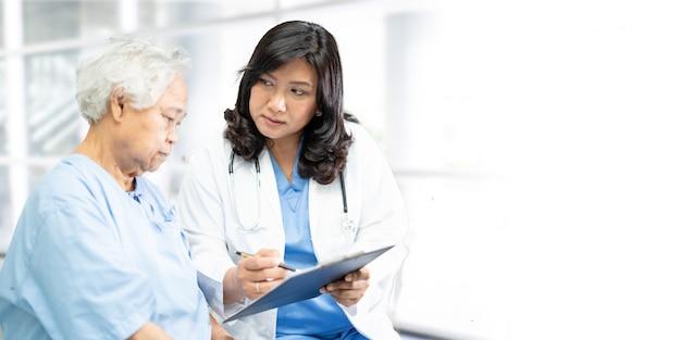 Lekarz rozmawia z pacjentem azjatyckich starszy kobieta w szpitalu z miejsca na kopię.