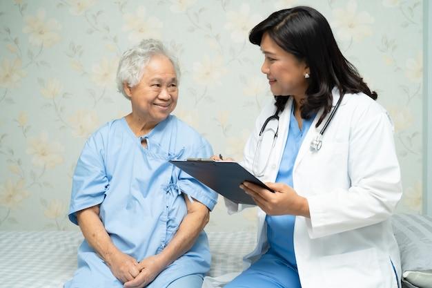 Lekarz rozmawia z pacjentem azjatyckim starszy kobieta w szpitalu.