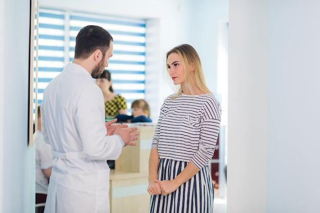 Lekarz rozmawia z pacjentem na korytarzu