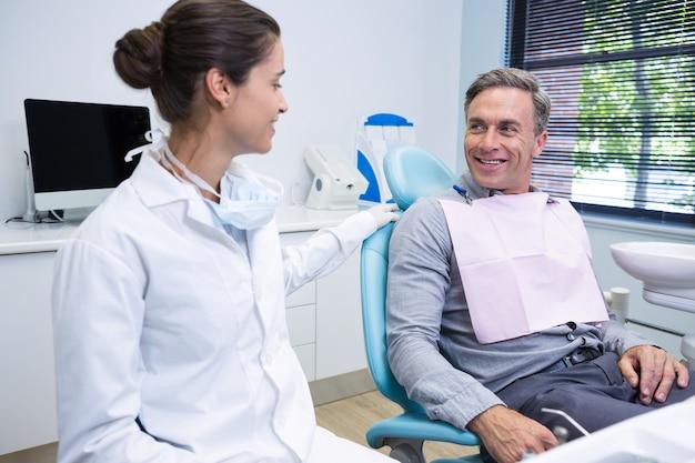 Lekarz rozmawia z pacjentem siedząc w przychodni