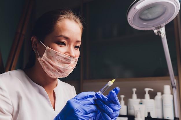 Lekarz rysuje punkt do wstrzyknięć na twarzy pacjenta. przygotowanie do biorewitalizacji z bliska.