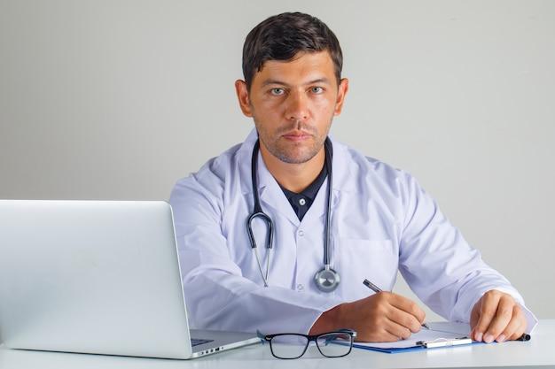 Lekarz siedzi i robienie notatek w białym fartuchu i stetoskopie
