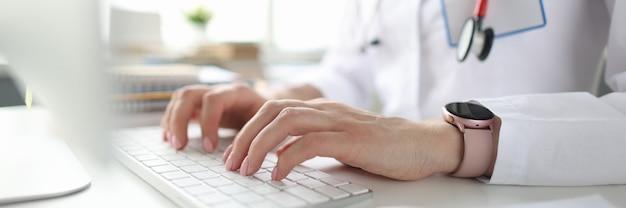 Lekarz siedzi przy stole i pisze na klawiaturze komputera zbliżenie