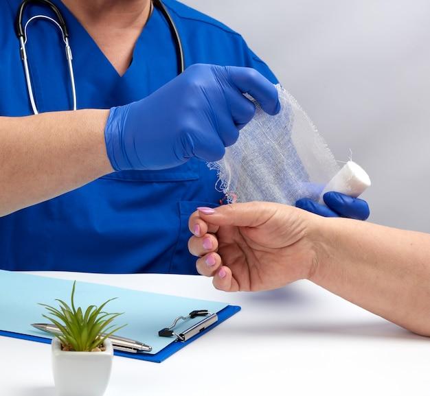 Lekarz siedzi przy stole w niebieskim mundurze i lateksowych rękawiczkach, specjalista bandażuje rękę białą bandażą dla pacjenta