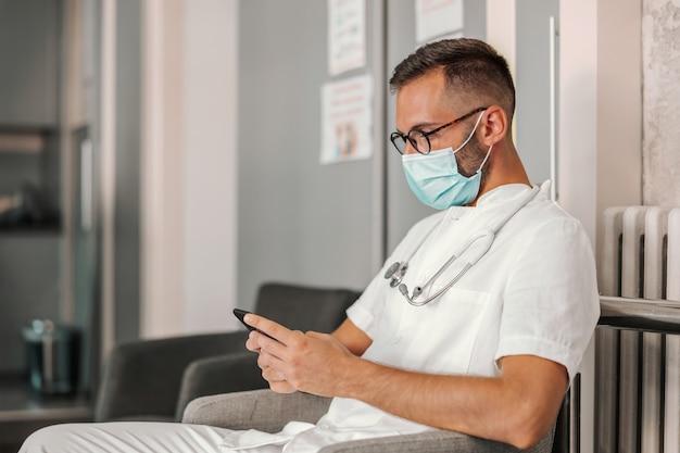 Lekarz siedzi w hali szpitala i używa inteligentnego telefonu do wysyłania wiadomości tekstowych w nagłych wypadkach.