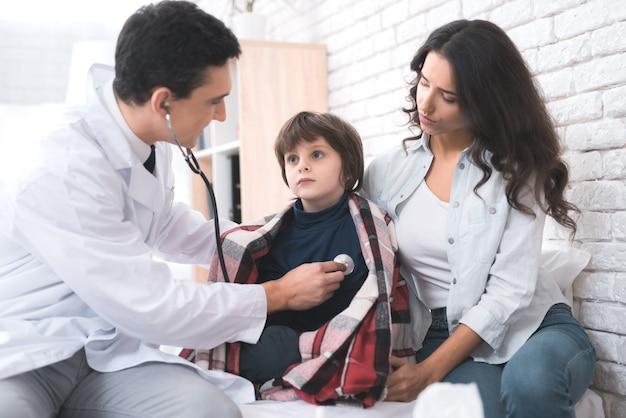 Lekarz słucha serca chorego chłopca w stetoskopie.
