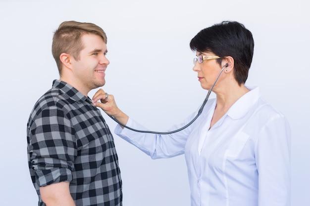 Lekarz słuchając klatki piersiowej wesoły młody pacjent ze stetoskopem na białym tle
