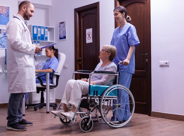 Lekarz specjalista omawiający diagnostykę i leczenie rekonwalescencji z niepełnosprawnym seniorem