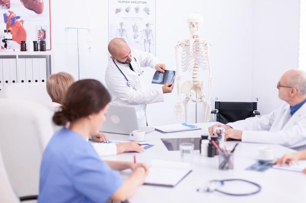 Lekarz specjalista posiadający radiografii podczas seminarium medycznego dla personelu medycznego w sali konferencyjnej. terapeuta kliniczny rozmawiający z kolegami o chorobie, specjalista od medycyny