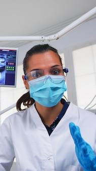 Lekarz specjalista rozmawia z pacjentem w klinice stomatologii, siedząc na krześle przed badaniem. stomatolog wyjaśniający problem stomatologiczny i leczenie profilaktyka stomatologiczna noszenie maski ochronnej