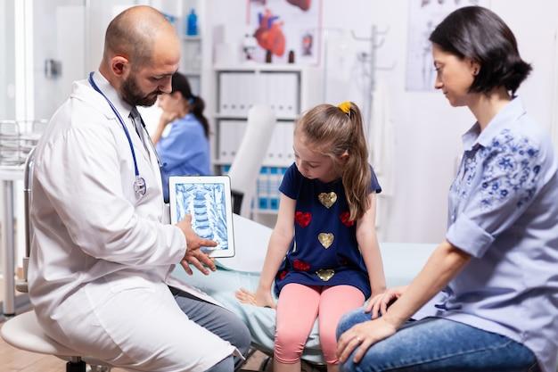 Lekarz specjalista trzymający tablet z rtg podczas badania dziecka w gabinecie szpitalnym. pediatra wyjaśniający leczenie choroby, świadczący usługi zdrowotne