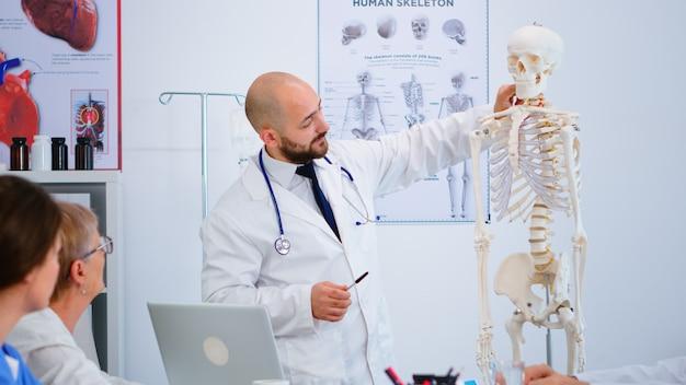Lekarz specjalista w białym fartuchu pokazujący kolegom funkcje kości ciała na modelu szkieletu. medyk wskazujący i wyjaśniający współpracownikom procedury medyczne siedząc w sali konferencyjnej szpitala.